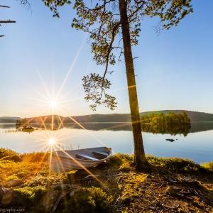 Reflection of the Midnight Sun on the calm Ukonjärvi lake in Lapland