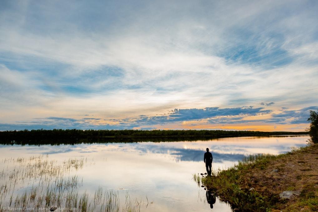Silhouette et autoportrait de Rayann Elzein debout sur la rive d'un lac au nord de la Finlande en été