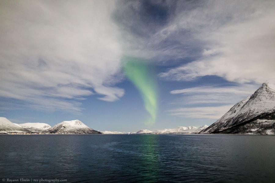 Aurores boréales à travers les nuages près de Tromsø